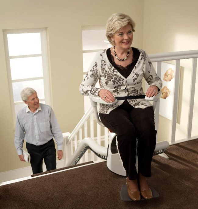 Person Sitting on The Flow2 Indoor Curved Rail Stairlift